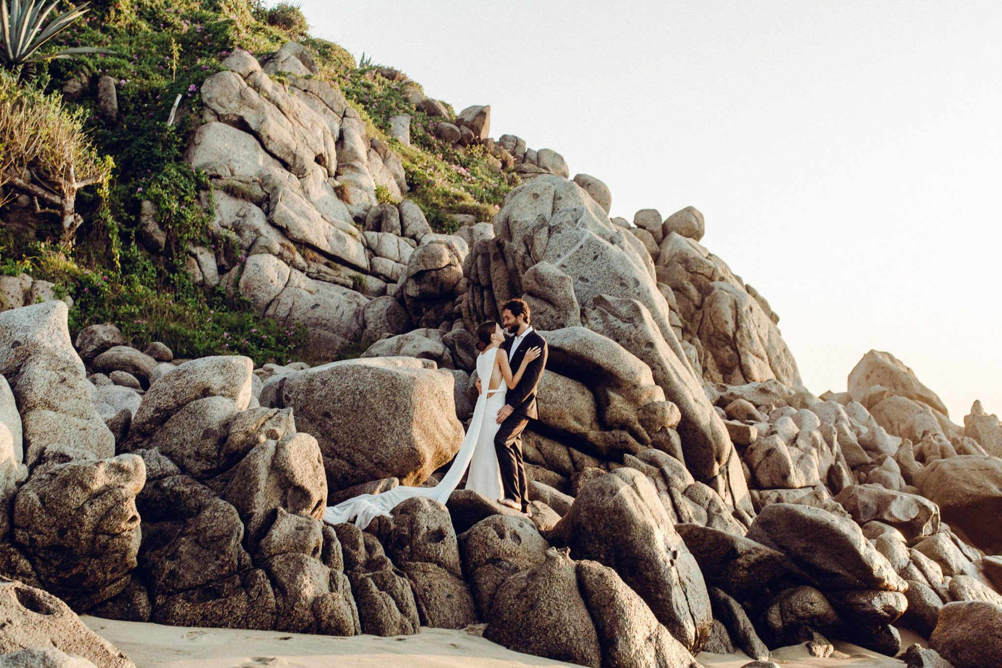 Dramatic photo of newlywed couple with the sun kissing his back and her train flowing over the rocks like water