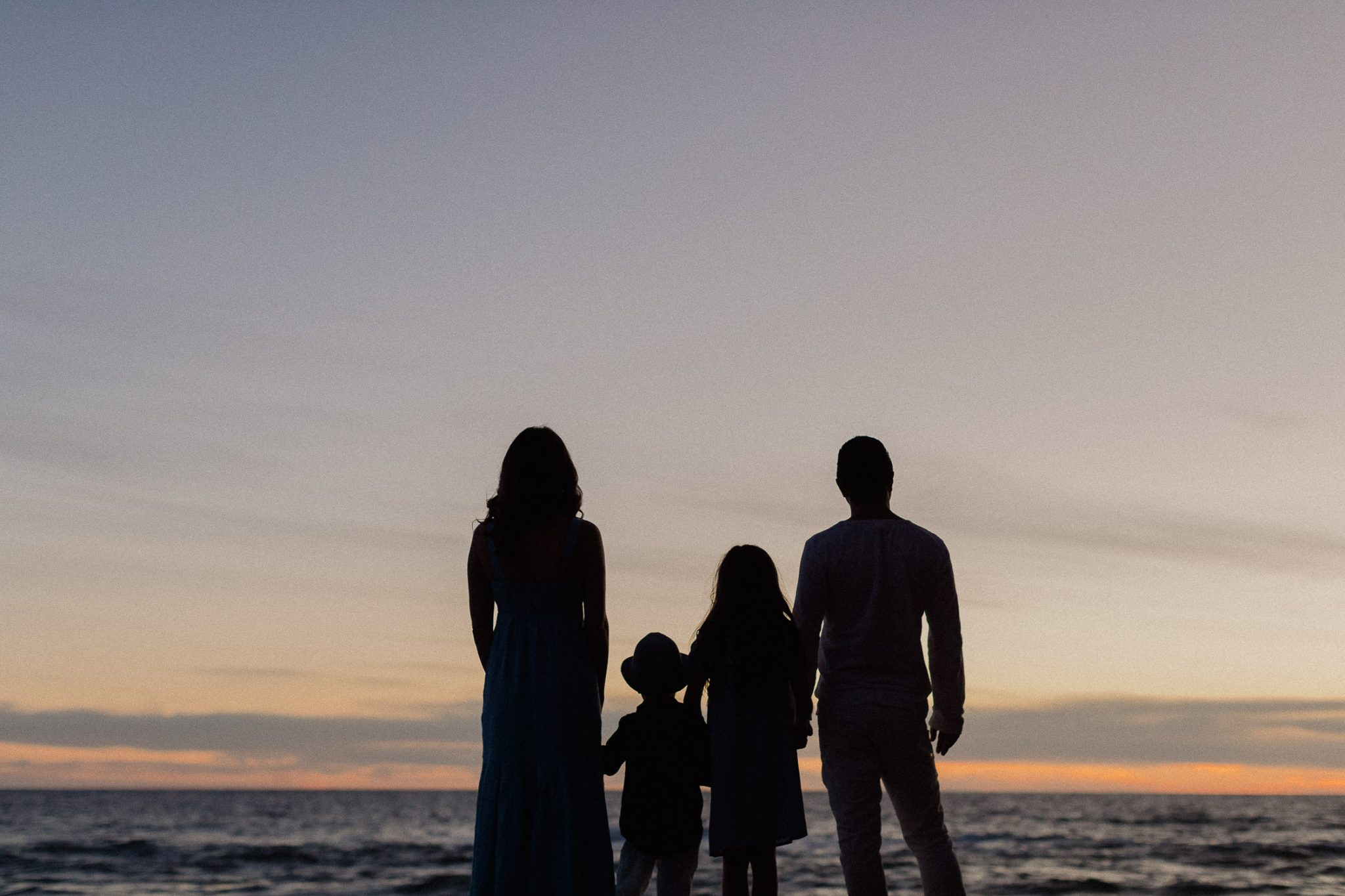 Silhouette family staring out at the horizon on the beach after sunset